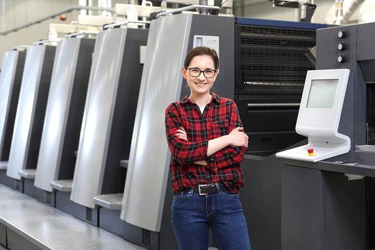 Praca w drukarni. Uśmiechnięta kobieta, pracownik drukarni stoi w hali produkcyjnej na tle nowoczesnych maszyn drukarskich