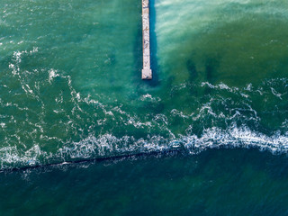 Natural sea background with turquoise water. Top aerial view from drone to moles and jetty with foam waves. Copy space.