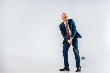 surprised mature businessman holding golf club while playing on grey
