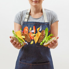 Female chef in a denim apron with flying tasty homemade burger from fresh natural ingredients in her hands on a white background. Place for text.