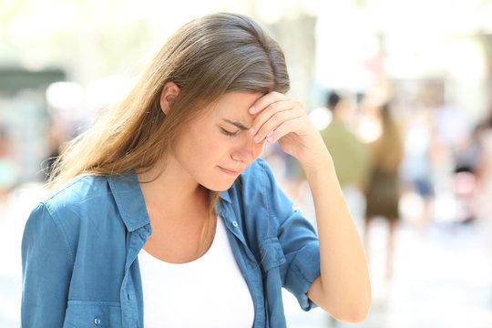 Girl suffering headache standing in the street