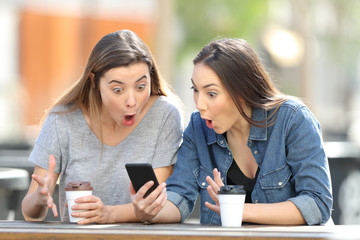 Surprised friends finding amazing phone online content