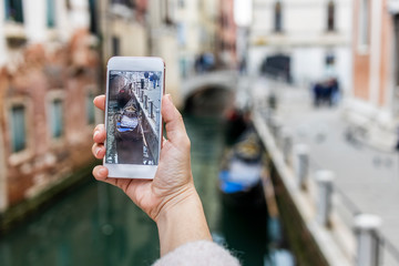 The hand of a woman taking a photo to a gondola in Venice