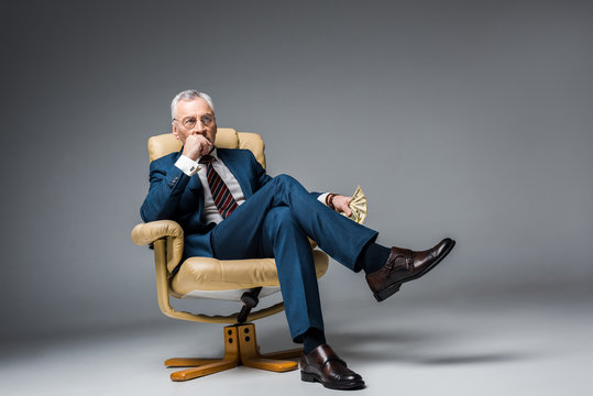 thoughtful mature businessman sitting in armchair and holding dollar banknotes on grey