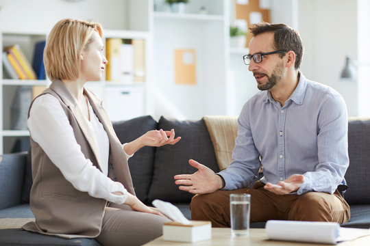 Confident counselor and his patient sitting on couch and discussing problems of young woman during session