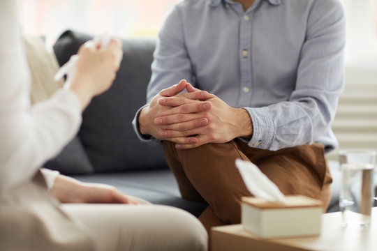 Crossed hands on knees of contemporary psychologist during discussion of patient problem on couch