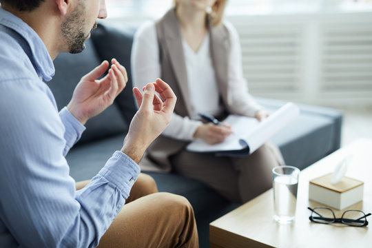 Young man explaining his problems to counselor while sitting in front of her by table with glass of water on edge