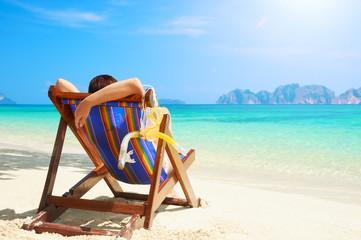 Summer beach vacation concept, woman enjoying on the beach chair of Phi Phi island, Thailand