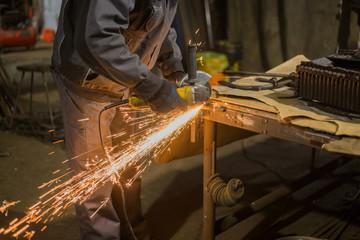 Professional blacksmith sawing metal with hand circular saw at forge, workshop. Handmade, craftsmanship and blacksmithing concept