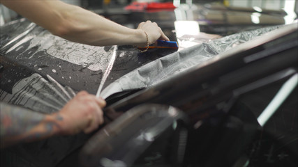 professional applying protective film to the red car. Master glues a protective film on the hood of the car