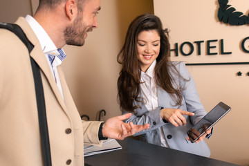 Fototapeta Young business man check-in in hotel, smiling female receptionist behind the hotel counter showing him available rooms on tablet. obraz
