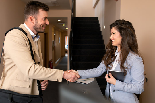 Young business man check-in in hotel shaking hands with female receptionist.