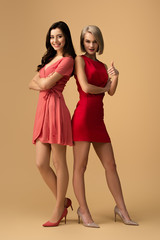 Full length view of women in red dresses with crossed arms showing thumb up on beige background