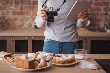 Food photographer. Blogging business. Man with tablet and camera. Cakes and pastries assortment around.