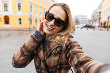 Beautiful young blonde woman wearing a coat
