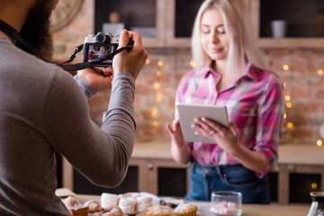 Online recipe. Blogging. Woman with tablet. Man shooting vlog episode on cakes and pastries cooking.