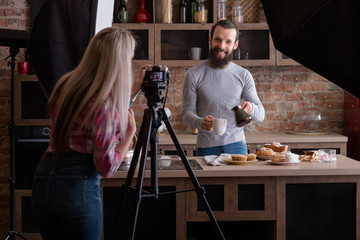 Lifestyle photographer at work. Woman shooting young man at loft kitchen. Coffee and pastries. Backstage photography.