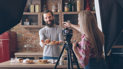 Homemade cooking. Baking hobby. Backstage photography. Woman shooting smiling man with fresh cakes and pastries.