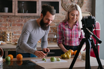 Vlog on healthy nutrition. Food blog. Young couple cutting fruit. Video recording at kitchen.