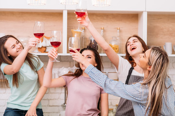 Cheers. Group of friends having home party. Weekend leisure. Urban lifestyle. Young women clinking red wine glasses.