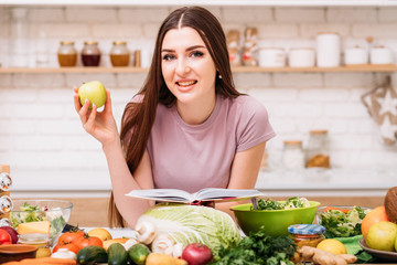 Healthy eating. Organic nutrition benefits. Young female with apple and book of vegetarian recipes.