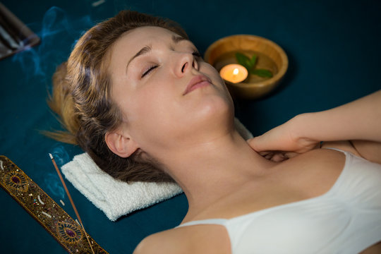 Woman with closed eyes Relaxing at home, lying on acupuncture mat. Candles and incense aroma sticks.