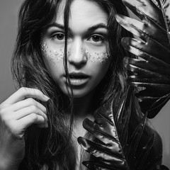 Natural woman beauty. Spa hair health care. Young female with monstera leaves. Focused stare. Black and white.