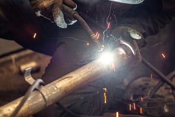 repairing of corrugation muffler of exhaust system in car workshop - serviceman welds the old silencer on car by argon welding