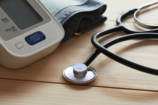 Close-up view of a stethoscope and a sphygmomanometer on wooden background