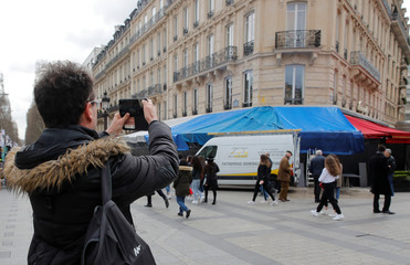 """A man takes pictures of the Fouquet's restaurant burned during the last """"yellow vests"""" protest on the Champs Elysees avenue in Paris"""