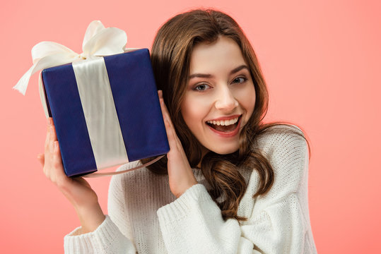 smiling and beautiful woman in white sweater holding gift box isolated on pink