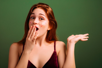 Excited young woman. Wow. Open mouth stare. Hand at lips. Virtual object in hand palm.