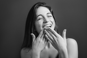 Pleasure. Young female shy at laughing hard. Toothy smile with hands on mouth. Eyes closed. Black and white portrait.