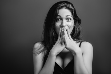 Amazed young woman with wide open eyes. Shock facial expression. Black and white portrait. Copy space.