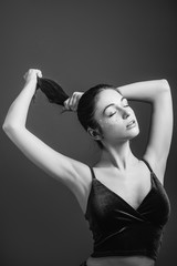 Young woman beauty. Posing female. Raised bare arms. Eyes closed. Black and white portrait. Copy space.