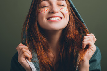 Beaming redhead female portrait. Youth beauty. Closed eyes. Toothy smile. Glitter freckles makeup.