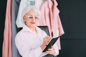 Fashion style assistance. Senior lifestyle. Confident elderly woman looking at camera while making notes in day planner.