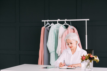 Successful seniority. Showroom clothes business. Confident elderly lady at workplace busy making notes in day planner. Copy space.