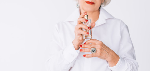 Elegance and fragrance. Senior woman holding bottle of expensive perfume. Copy space on white background.