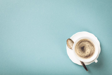 White cup of coffee on blue background with copy space for text. Top view.