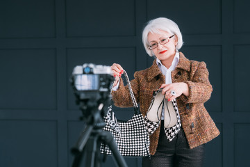 Senior fashion stylist blogger. Lifestyle elegance look. Aged lady in trendy autumn outfit shooting vlog.