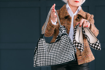 Trendy senior wardrobe. Female style and elegance. Aged lady in fashion autumn outfit showing bag and shoes.