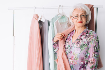 Confident senior lady at work. Fashion boutique business. Successful elderly lady posing by rack of showroom clothing.