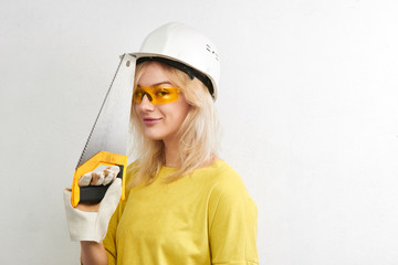 Sexy blonde engineer in construction helmet and glasses posing with saw in hand on white background with copy space. Builder, repair concept