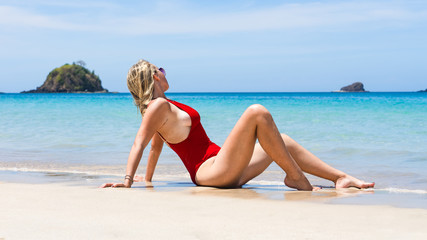 Beautiful Young Blonde Girl Relaxing In the Shoreline on the tropical Beach of Nacpan In El Nido, Palawan, Philippines