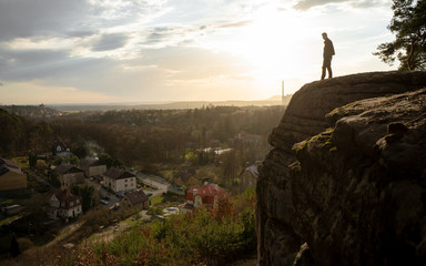 Adventurous man is standing on the edge of a rock and enjoying the beautiful view during a vibrant sunset. Taken on top Devil's heads - 9 m high rock statues, Zelizy village, Central Bohemian region,