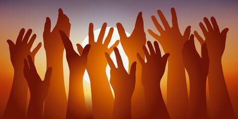 Concept de l'adhésion avec un groupe de mains levées devant un coucher de soleil, pour symboliser le vote de cohésion.