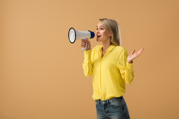 Smiling blonde woman in yellow shirt screaming in megaphone isolated on beige