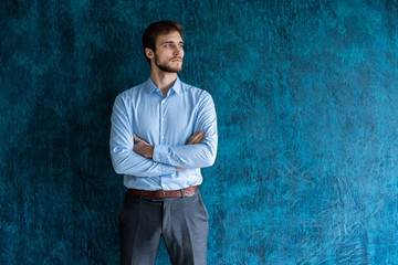 Portrait of handsome young man standing against blue wall with copy space.