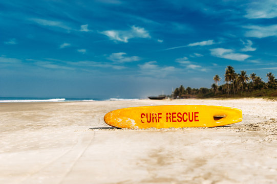 Bright yellow surfboard in the form of a pointer with a red word rescue on a sandy beach in the afternoon. Life saving yellow board with surf rescue sign. Rescue surf board
